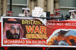 Demonstrators wave placards from an open top bus during a protest against the visit by Saudi Arabia's Crown Prince Mohammad bin Salman in central London