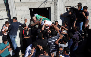 Mourners carry the body of a Palestinian, who was killed during a protest at the Israel-Gaza border, during his funeral in Khan Younis in the southern Gaza Strip