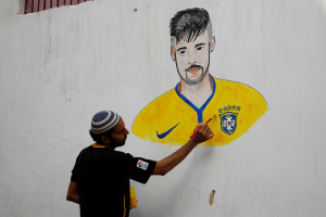A soccer fan, Mohammad Saleh, 38, paints on a wall depicting the Brazilian footballer Neymar, ahead of the FIFA World Cup Russia, in a low-income neighbourhood in Karachi