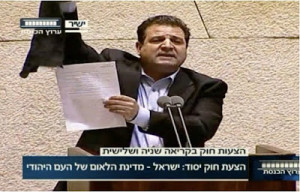 mp ayman odeh raises a black banner   during discussion in parliament